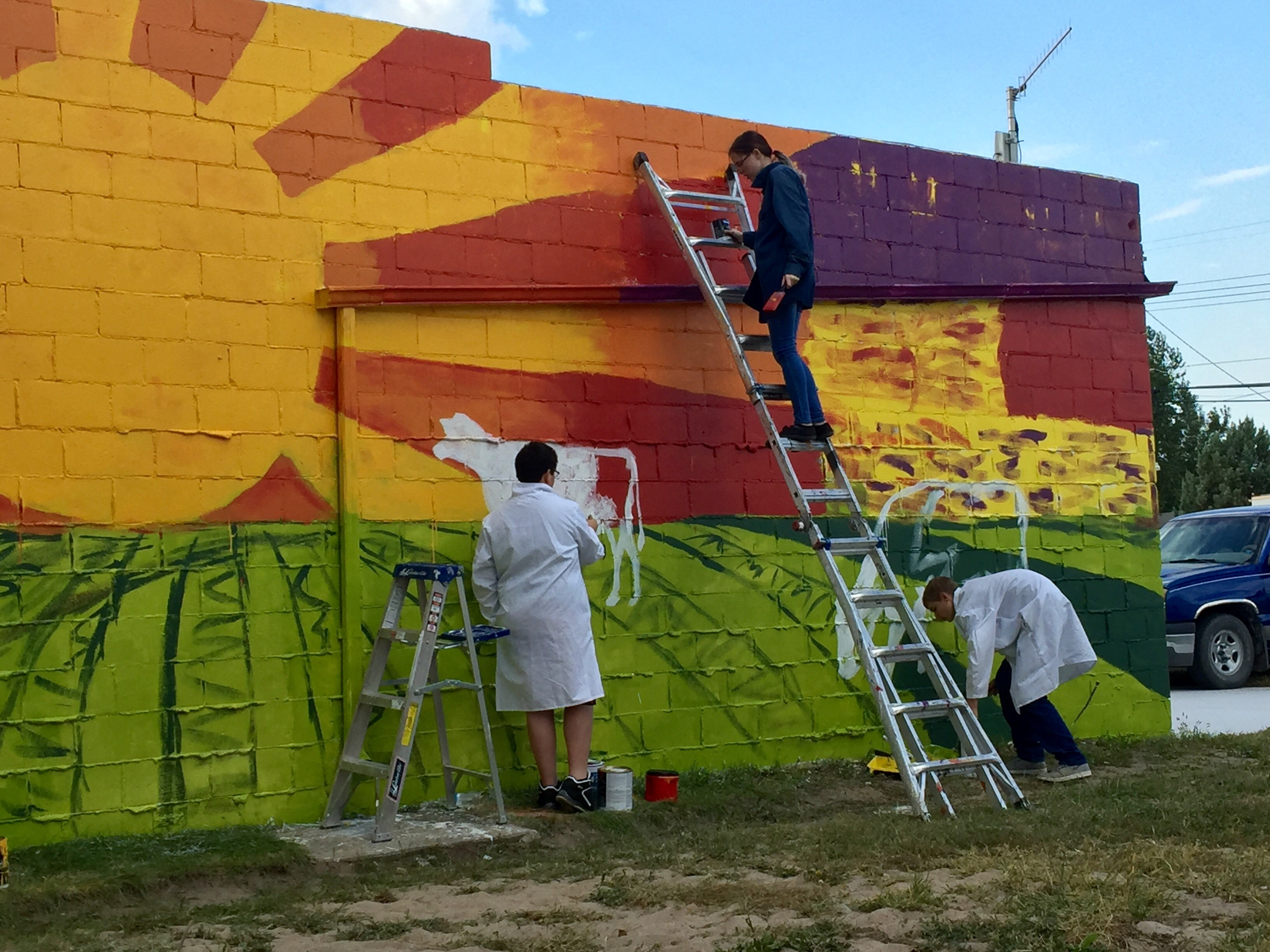 Image of students painting a mural on ladders