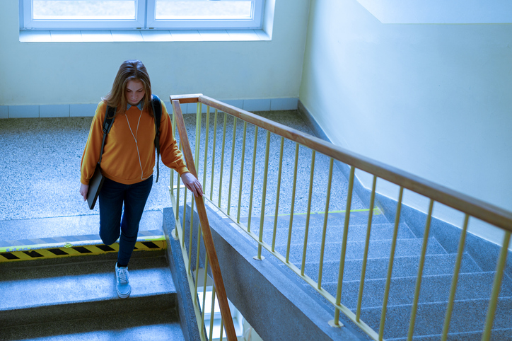 A female student gazes downward as she walks alone along a school corridor.