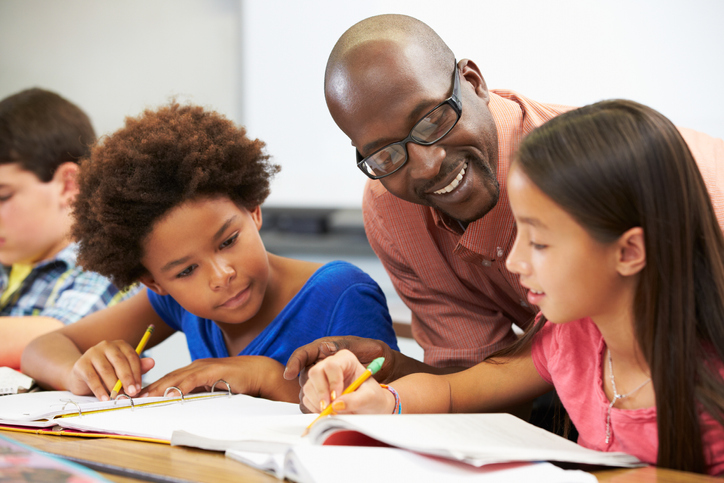 A teacher sits with kids.