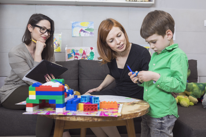 Two teachers watch a young boy play.