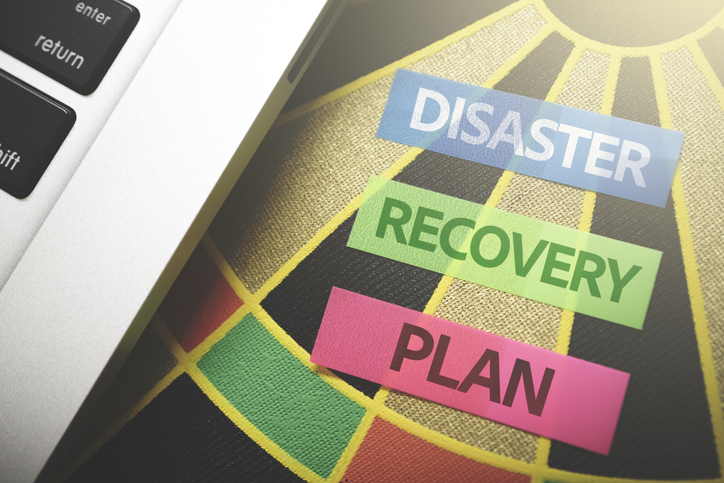 """Computer on top of a dartboard with the words """"Disaster"""", """"Recovery"""", and """"Plan"""" cut out from construction paper."""