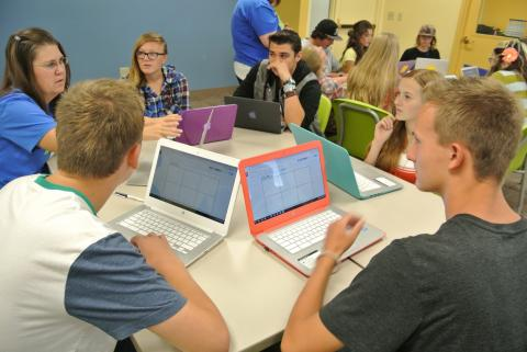 Group of students at a table discussion with laptop computers